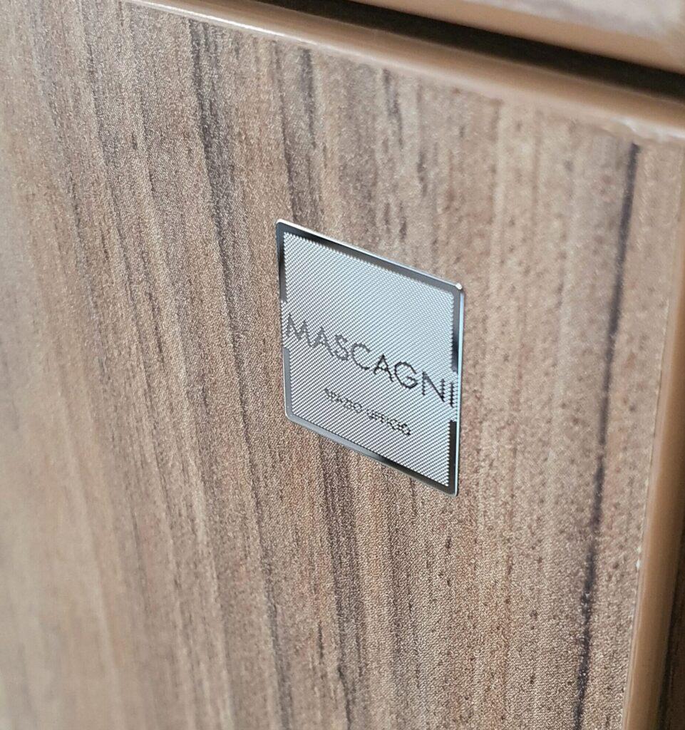 etichetta cromata su mobile legno